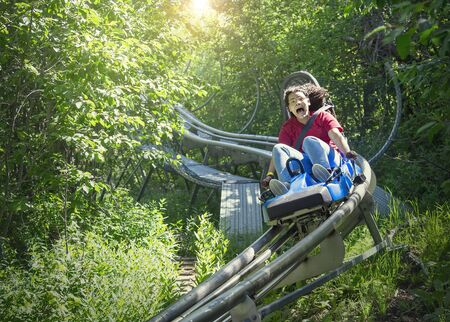 Screaming teen girl riding downhill on an outdoor roller coaster on a warm summer day. She has a fun expression on her face as she enjoys a thrilling ride on an amusement park ride Stock fotó