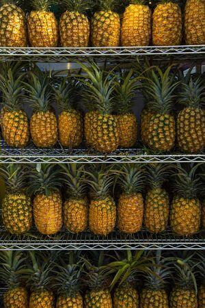 Pineapples on shelves in market ready for sale. Pineapple background. Stock fotó