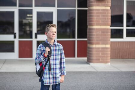 Candid portrait of a male elementary school student standing outside the school building. Handsome boy with his backpack heading home from school at the end of the day