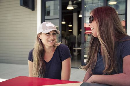 Two women talking and smiling together as they sit at an outdoor cafe in a retail mall. Girlfriends having fun together shopping and eating Category Lifestyle