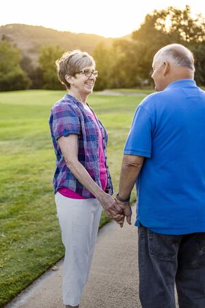 A loving senior couple on a walk together at sunset. Still in love after all these years. Smiling women holding the aged hand of her husband walking together outdoors