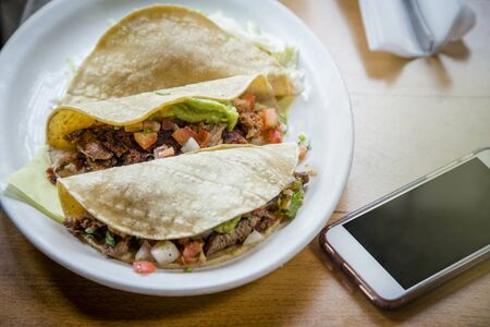 Three delicious tacos on a plate sitting next to a cell phone at a Mexican food restaurant. Concept of ordering your food and lunch online