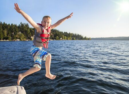 Boy jumping into a beautiful mountain lake. Having fun on a summer vacation. Having fun on a summer vacation. Excited expression on his face and arms raised high Stock fotó