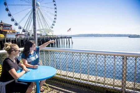 Two women looking out at the Seattle harbor on a sunny day. Sitting at a table on the waterfront near the Ferris Wheel and pier Stock fotó