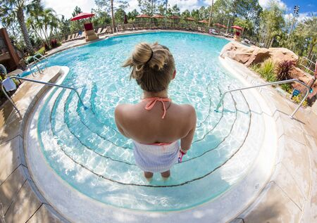 View from behind of a woman entering in a luxurious outdoor swimming pool at a beautiful resort. Unique wide angle photo of a person enjoying a special vacation Stock fotó