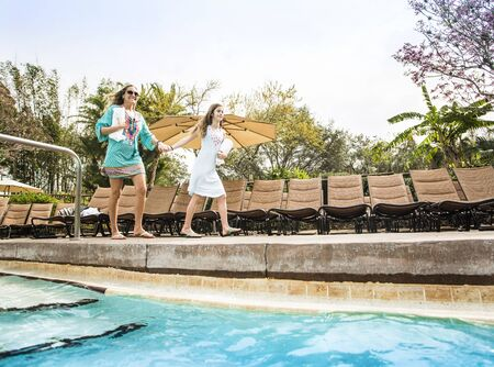 Low angle view of two people entering in a luxurious outdoor swimming pool at a beautiful resort. Unique low angle photo of two people enjoying a special vacation