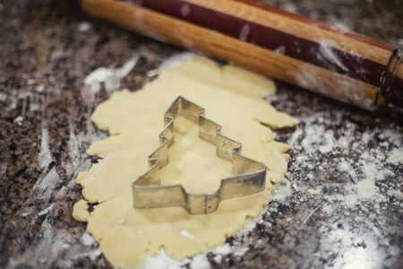 Preparing Christmas cookies using cookie cutters and a rolling pin to prepare the dough. Selective focus on the cutter and sugar cookie dough