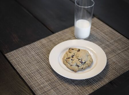 Delicious chocolate chip cookie on a plate and a glass of milk sitting on a table