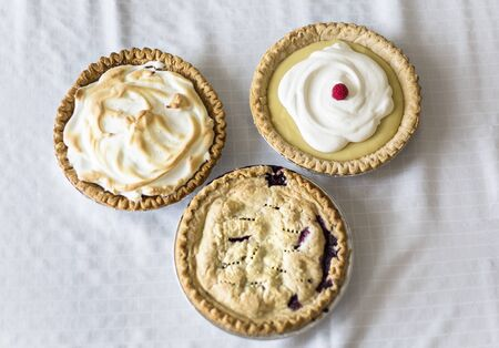 Assorted delicious whole Pies sitting on a table. A view of three different homemade pies - Lemon Meringue, cream and berry pies.