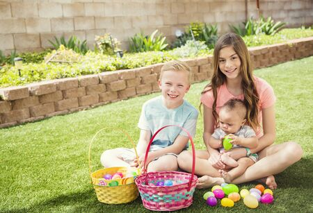 Easter Holiday lifestyle photo. Three cute smiling kids collecting eggs on an Easter Egg hunt outdoors in the yard. They are working together to put the eggs in their baskets