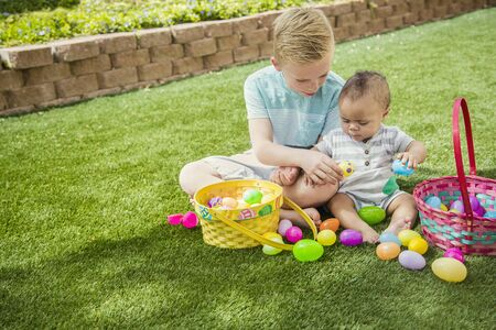 Two Cute little boys collecting eggs on an Easter Egg hunt outdoors in the yard. working together to put the eggs in their baskets