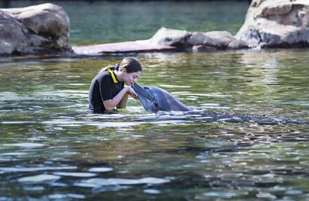 Cute teenage girl kissing a bottlenose dolphin on the nose in a beautiful ocean lagoon. Young girl loving Marine life in a natural setting