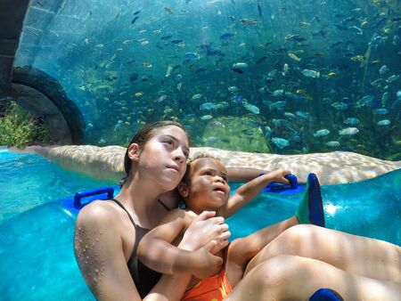 Two cute kids on an inflatable tube at a water park looking up at the fish in a large aquarium all around them. Lifestyle photo of a beautiful scenic vacation experience Stock fotó