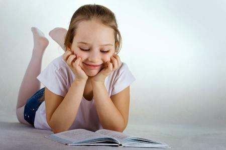 niños leyendo: Niña lieyng en el suelo y la lectura del libro Foto de archivo