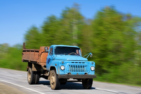 Blue old truck running along the road photo