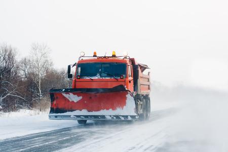 Snowplow working in winter snow storm photo
