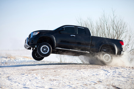 Black truck traveling in the snow and jumping photo
