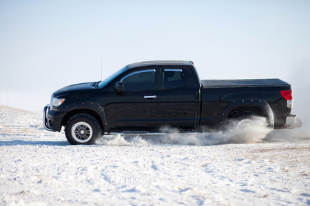 Black truck traveling in the snow  photo