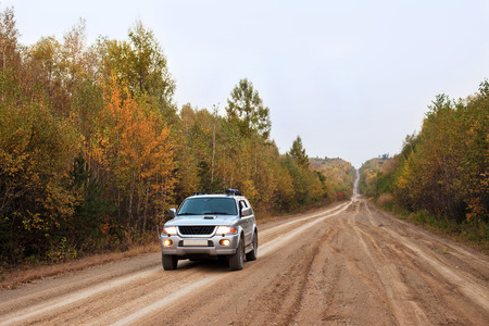 4x4 car stopped its run to make a photo in this beautiful autumn forest