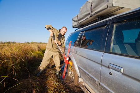 Man lifting stucked car by hi jack photo
