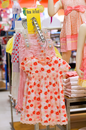 garderobe: Different little girl dress on hangers in a shop