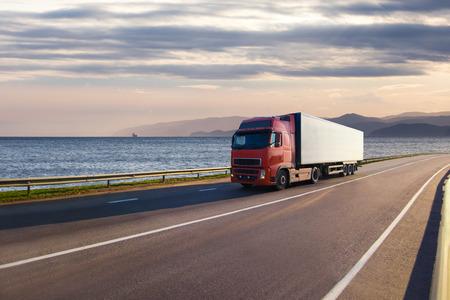 海の近くの道路上の赤いトラック 写真素材