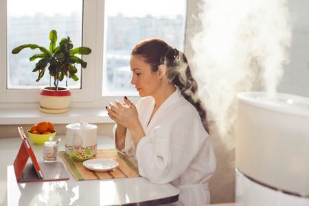 humidifier: Woman drinking tea reading tablet near humidifier