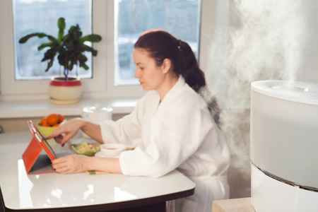 ionizing: Woman sitting at the table on the background of humidifier Stock Photo