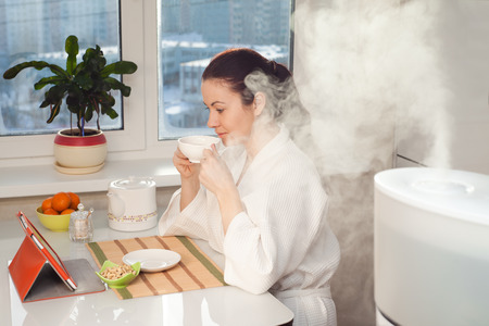 Woman drinking tea reading tablet near humidifier