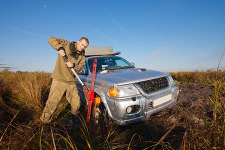 lifting jack: Man lifting stucked car by hi jack