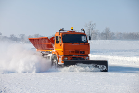 Snowplow is cleaning a road and snow flying around it Standard-Bild