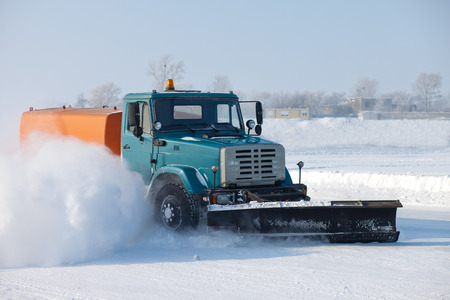 drifting ice: Snowplow is cleaning a road and snow flying around it Stock Photo