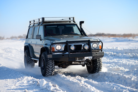 suv: Classic SUV traveling in the snow Stock Photo