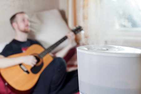 ions: Man playing guitar on the blured background of humidifier Stock Photo
