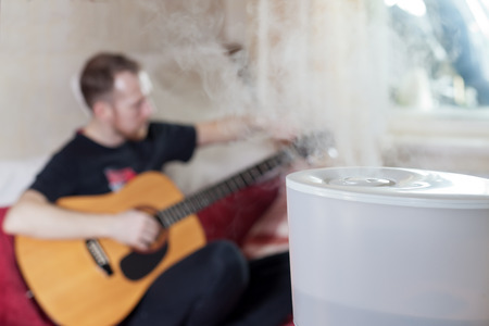humidifier: Man tuning his guitar on the blured background of humidifier Stock Photo