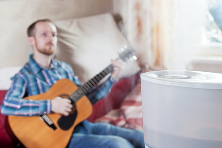 humidifier: Man playing guitar on the blured background of humidifier Stock Photo