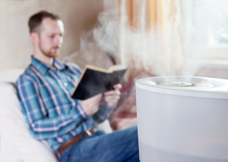 Man reading book on the blured background of humidifier Фото со стока