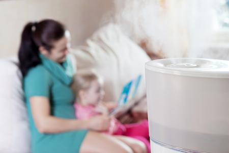 Mutterlesebuch zu ihrer Tochter auf dem blured Hintergrund der Luftbefeuchter Standard-Bild - 37444590