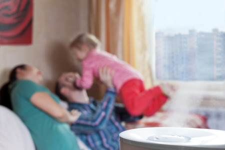 ionizing: Parents playing with their daughter on the blured background of humidifier Stock Photo