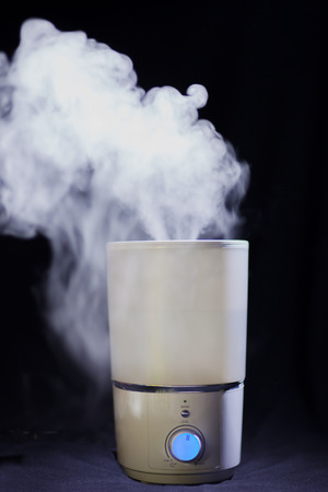 humidifier: Humidifier spreading steam in a dark room Stock Photo