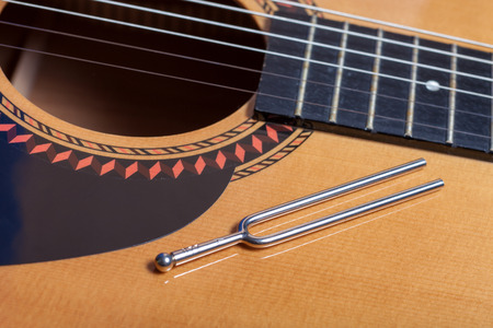 tuning fork: Music tuning fork on acoustic guitar
