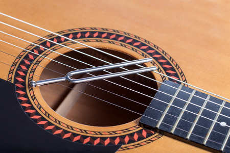 tuning fork: Music tuning fork on acoustic guitar strings