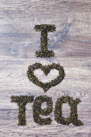 raw tea: Words I love you made of green tea leaves on wood background Stock Photo