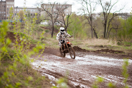 motorsprot: Motocross rider moving on a mud track