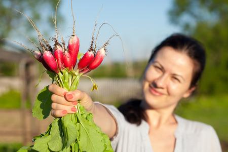 dacha: Woman shows a radish sheaf that grows at her dacha