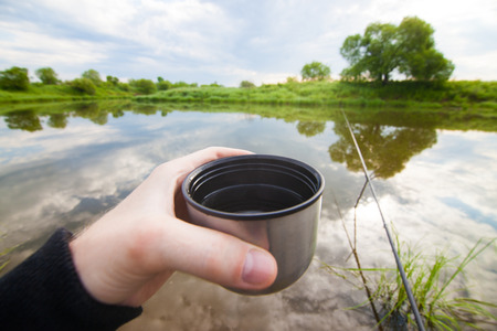 fisherman: Fisherman is going to drink tea from thermos during fishing Stock Photo