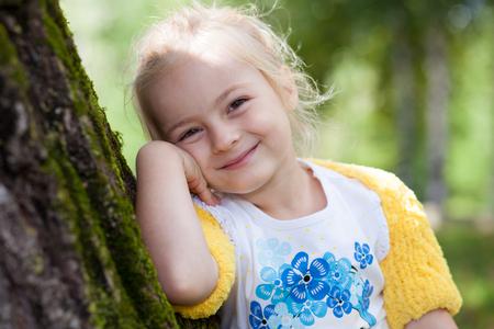 bolero: Cute little girl in knitted yellow bolero posing at a tree