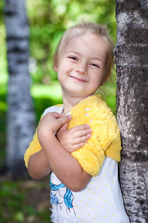 face in tree bark: Cute little girl in knitted yellow bolero posing at a birch Stock Photo