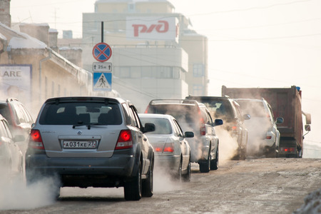 KHABAROVSK, RUSSIA - JANUARY 5, 2011: Cars moving on ice winter road spreading exhaust. Редакционное