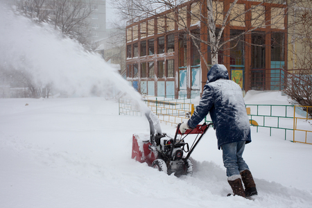 blow: KHABAROVSK, RUSSIA - DECEMBER 03, 2015: A man removing snow with a snowblower during snowstorm